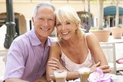 Senior Couple Enjoying Coffee And Cake In Café - stock photo