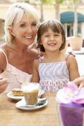 Grandmother With Granddaughter Enjoying Coffee And Cake In Café - stock photo