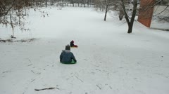 Two children down steep hill with snow pad nice winter afternoon Stock Footage