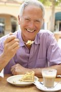 Senior Man Enjoying Coffee And Cake In Café - stock photo