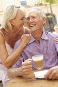 Senior Couple Enjoying Coffee And Cake In Café Stock Photos