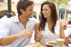 Young Couple Enjoying Coffee And Cake In Café - stock photo