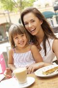 Mother And Daughter Enjoying Cup Of Coffee And Piece Of Cake In Café Stock Photos