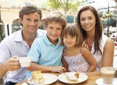 Young Family Enjoying Cup Of Coffee And Cake In Café Together - stock photo