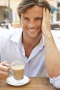 Young Man Enjoying Cup Of Coffee In Café - stock photo