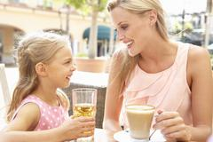 Mother And Daughter Enjoying Cup Of Coffee And Juice In Café Together - stock photo