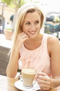 Young Woman Enjoying Cup Of Coffee In Café - stock photo