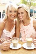 Two Women Enjoying Cup Of Coffee In Café Stock Photos