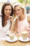Two Young Women Enjoying Cup Of Coffee In Café - stock photo