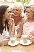 Three Women Enjoying Cup Of Coffee In Café - stock photo