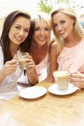 Three Women Enjoying Cup Of Coffee In Café Stock Photos