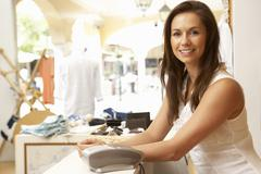 Female Sales Assistant At Checkout Of Clothing Store Stock Photos