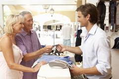 Male Sales Assistant At Checkout Of Clothing Store With Customers Stock Photos