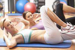 Women Doing Stretching Exercises In Gym Stock Photos