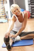 Senior Woman Doing Stretching Exercises In Gym Stock Photos