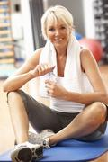 Senior Woman Resting After Exercises In Gym - stock photo