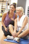Woman Doing Stretching Exercises In Gym With Trainer Stock Photos
