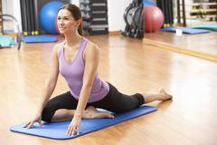 Woman Doing Stretching Exercises In Gym - stock photo