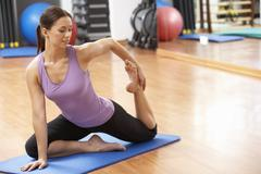Woman Doing Stretching Exercises In Gym Stock Photos