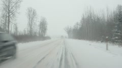cars going slippery rural road winter snow snowstorm falling - stock footage