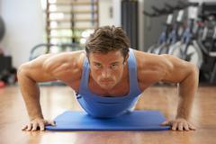 Man Doing Press Ups In Gym Stock Photos