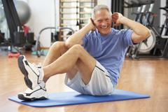 Senior Man Doing Sit Ups In Gym Stock Photos