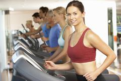 Woman On Running Machine In Gym Stock Photos