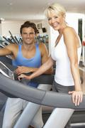 Senior Woman Working With Personal Trainer On Running Machine In Gym - stock photo