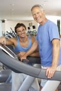 Man Working With Personal Trainer On Running Machine In Gym Stock Photos