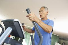 Senior Man On Cross Trainer In Gym - stock photo