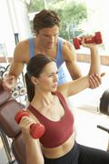 Young Woman Working With Weights In Gym With Personal Trainer Stock Photos
