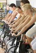 Woman Cycling In Spinning Class In Gym - stock photo
