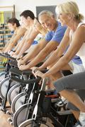 Senior Man Cycling In Spinning Class In Gym - stock photo