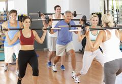 Group Of People Lifting Weights In Gym - stock photo