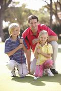 Father Teaching Children To Play Golf On Putting On Green Stock Photos