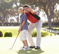 Father Teaching Son To Play Golf On Putting On Green Stock Photos