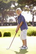 Young Boy Practising Golf On Putting On Green Stock Photos