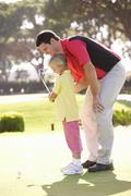 Father Teaching Daughter To Play Golf On Putting On Green Stock Photos