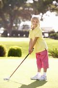 Young Girl Practising Golf On Putting On Green Stock Photos