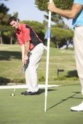 Male Golfer On Golf Course Putting On Green Stock Photos