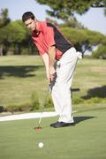 Male Golfer On Golf Course Putting On Green - stock photo