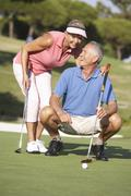 Senior Couple Golfing On Golf Course Lining Up Putt On Green Stock Photos