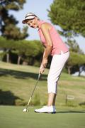 Senior Female Golfer On Golf Course Lining Up Putt On Green Stock Photos