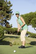 Female Golfer On Golf Course Putting On Green Stock Photos