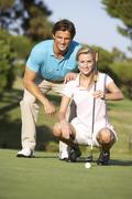 Couple Golfing On Golf Course Lining Up Putt On Green Stock Photos