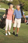 Senior Couple Walking Along Golf Course Carrying Bags Stock Photos