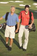 Two Men Walking Along Golf Course Carrying Bags - stock photo