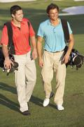 Two Men Walking Along Golf Course Carrying Bags Stock Photos