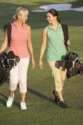 Two Women Walking Along Golf Course Carrying Bags Stock Photos