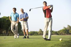 Group Of Male Golfers Teeing Off On Golf Course - stock photo